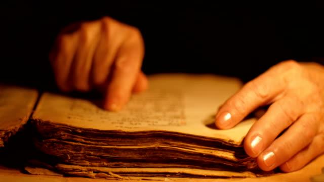 vídeos de stock e filmes b-roll de elderly woman reading old book - carta documento