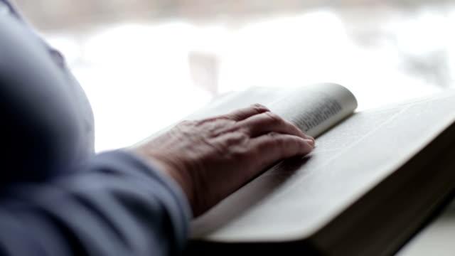 äldre kvinna läser bibeln hemma - kristendom bildbanksvideor och videomaterial från bakom kulisserna
