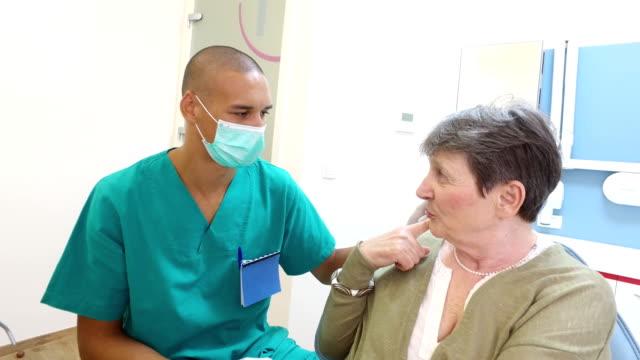 äldre kvinna visar värkande tanden till manliga tandläkare - two dentists talking bildbanksvideor och videomaterial från bakom kulisserna