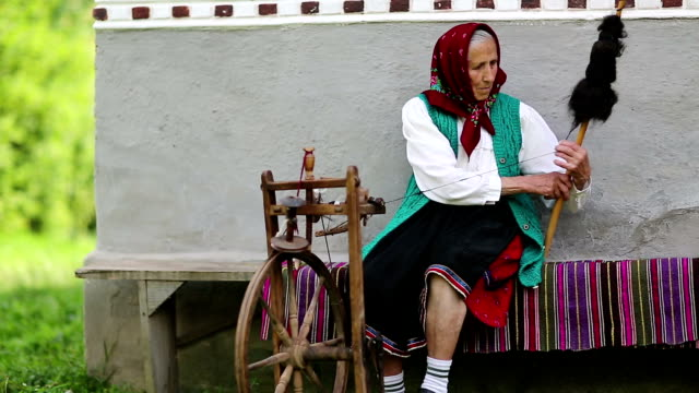 Elderly woman sits on bench and works with distaff, with spinning wheel video
