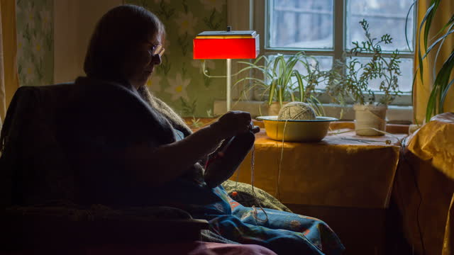 Elderly woman sitting in armchair and knitting a sock