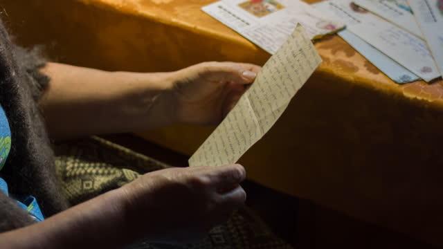 vídeos de stock, filmes e b-roll de idosa sentada em poltrona e lendo cartas antigas - correio correspondência