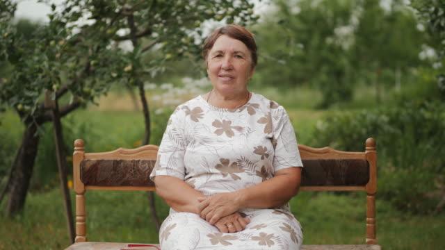庭のベンチに座っている高齢女性 - ベンチ点の映像素材/bロール