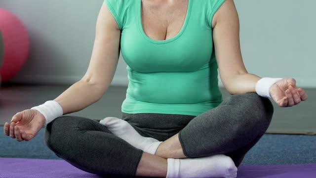 高齢者の女性の内側のバランス、体の健康ヨガ マットあぐらの上に座って - 女性選手点の映像素材/bロール