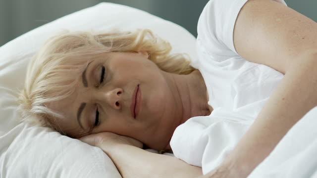 vídeos de stock e filmes b-roll de elderly woman sleeping with head resting on pillow, health improvement resort - upgrade