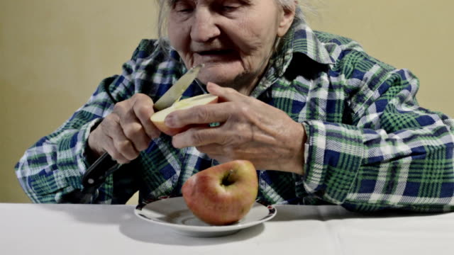 Elderly woman slicing an apple video