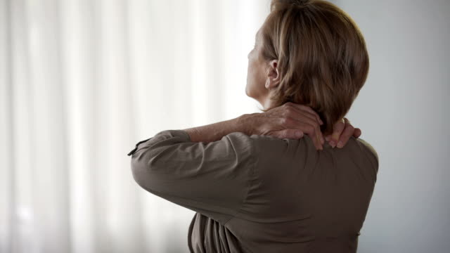 Elderly woman standing backwards, rubbing neck and shoulders, stiff muscles video
