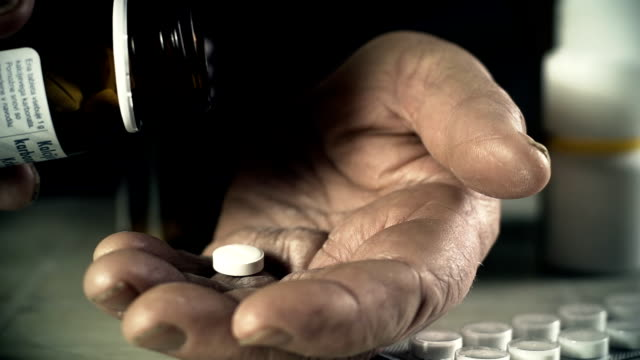 HD SLOW MOTION: Elderly Woman Taking A Pill HD1080p: SLOW MOTION shot of a senior woman spilling a pill out of a pill bottle into her palm. Close up shot of her hands. pill bottle stock videos & royalty-free footage