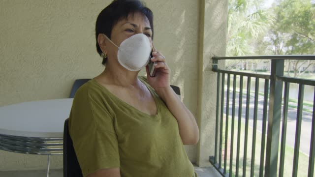 Elderly woman talking on the phone while wearing face mask video