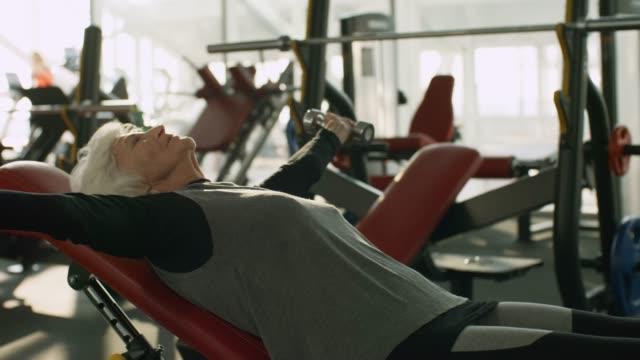 äldre kvinna träning med hantlar i gymmet - styrketräning bildbanksvideor och videomaterial från bakom kulisserna