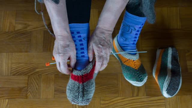 Elderly woman tries on leg sock from wool yarn