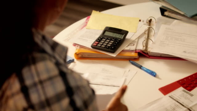 Elderly Woman Using Calculator For Taxes And Budget At Home