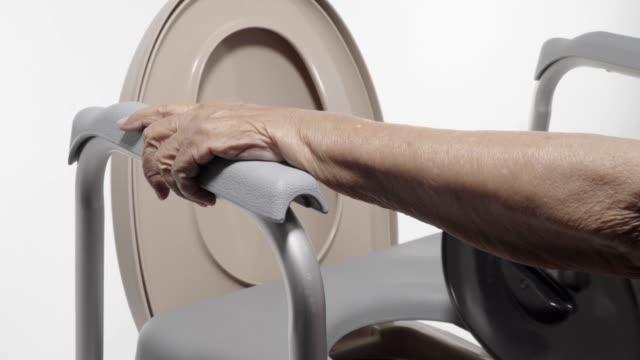 vídeos de stock, filmes e b-roll de mulher idosa que usa a cadeira móvel do assento do toalete - geriatria