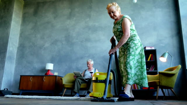 elderly woman vacuuming the floor, and an elderly man reading a newspaper and drink vine video