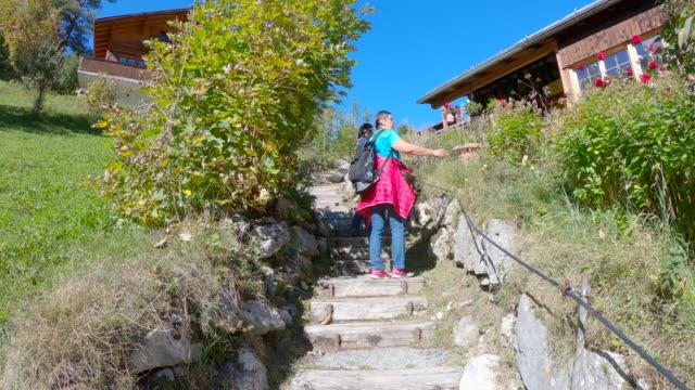 elderly woman walking up stairs through alpine village - время дня стоковые видео и кадры b-roll