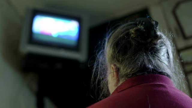 vídeos de stock e filmes b-roll de elderly woman watching television at home small tv mounted on the wall - tv e familia e ecrã