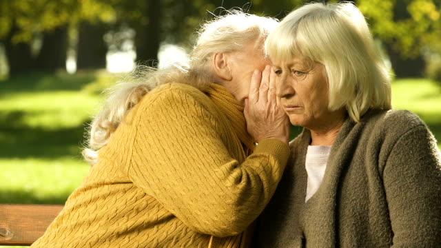 seniorin flüsternde gerücht, freund, skandalöse nachricht schockiert rentner - klatsch stock-videos und b-roll-filmmaterial