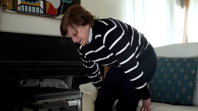 elderly woman with back pain gets up laboriously from the couch - fare la lotta video stock e b–roll