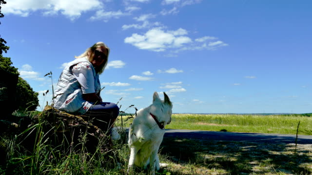Elderly woman with dog sits on a bench in spring