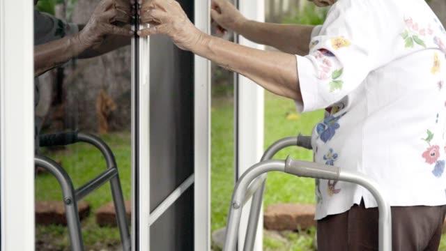 vídeos de stock, filmes e b-roll de mulher idosa com porta dianteira chave da abertura. - geriatria