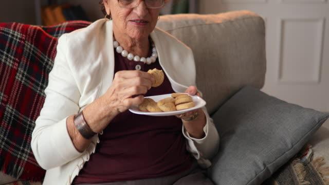 vídeos de stock, filmes e b-roll de mulher idosa com prato de biscoitos, comer biscoito delicioso em casa. - comida feita em casa