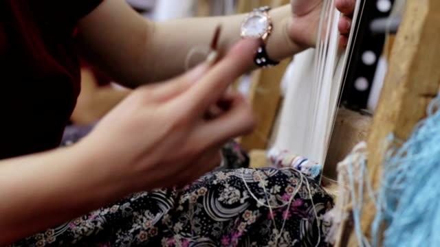 elderly woman working at weaving an Oriental rug: traditional turkish carpet video