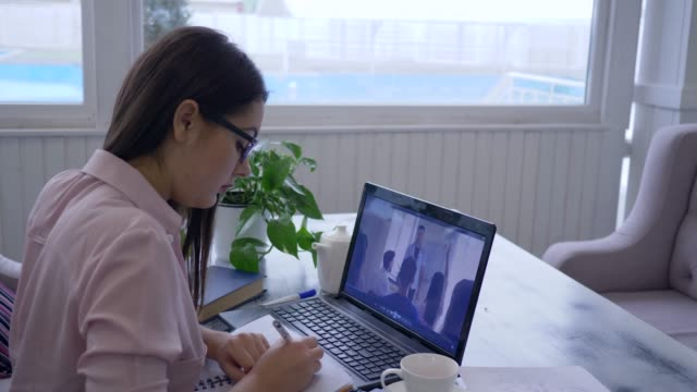 e-learning, young female spectacled passes online teaching for self-development uses laptop computer and makes notes in notebook - online learning stock videos & royalty-free footage