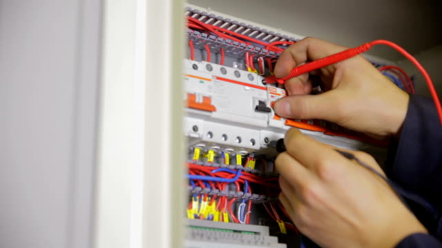 Electric Breaker Box. Electrician testing and switching fuse, breaker in a fuse box