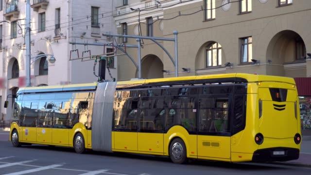 l'autobus elettrico scarica la batteria per strada in città - autobus video stock e b–roll