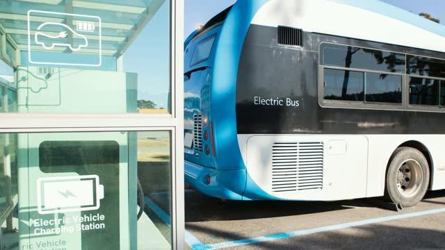 l'autobus elettrico si trova alla stazione di ricarica. - autobus video stock e b–roll