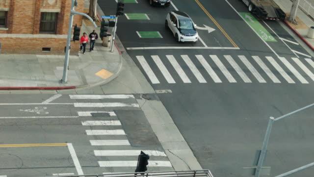 vídeos y material grabado en eventos de stock de coche eléctrico en de un paso peatonal visto desde arriba el centro de la ciudad de los ángeles - señalización vial