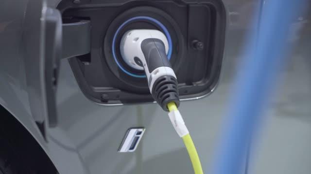 carburante per la ricarica di auto elettriche presso la centrale elettrica - carica elettricità video stock e b–roll
