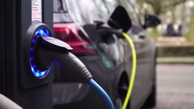 vidéos et rushes de voiture électrique de charge sur un parking à amsterdam - électricité
