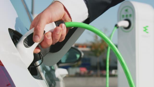 electric car charging - carica elettricità video stock e b–roll