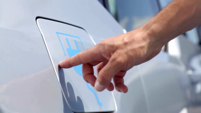 Electric car charging Color footage of a man's hand opening the lid of an electrical car, for charging. network connection plug stock videos & royalty-free footage
