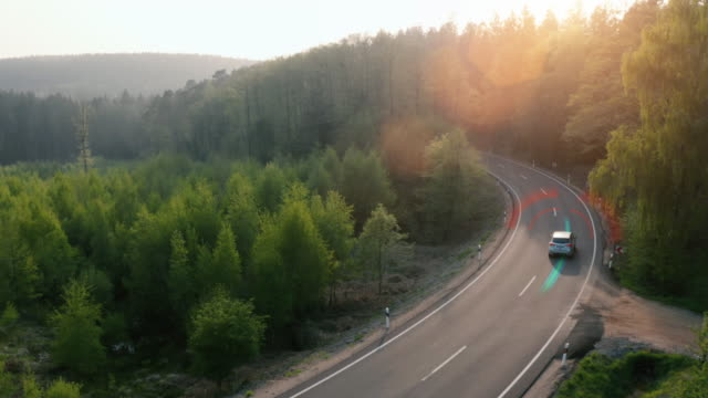 技術アシスタント追跡情報を持つ森林高速道路を走行する電気自動車は、詳細を示しています。視覚効果クリップ - 電気自動車点の映像素材/bロール