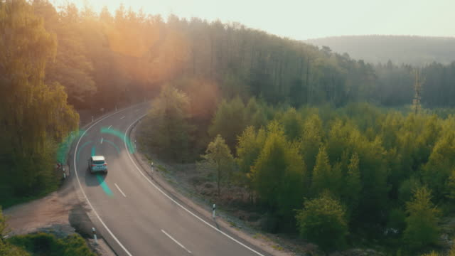 Electric car driving on a forest highway with technology assistant tracking information, showing details. Visual effects clip