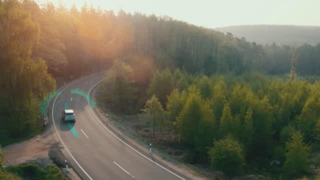 vídeos y material grabado en eventos de stock de coche eléctrico conduciendo por una carretera forestal con información de seguimiento de asistente de tecnología, mostrando detalles. clip de efectos visuales - dirección