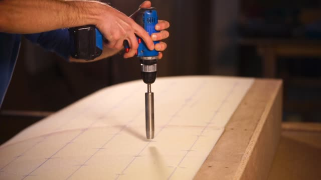 Electric drill with a special nozzle Handy man is holding electric tool with a special drill to make holes in couch filler. He is carefully drilling holes in a soft filler. handbook stock videos & royalty-free footage