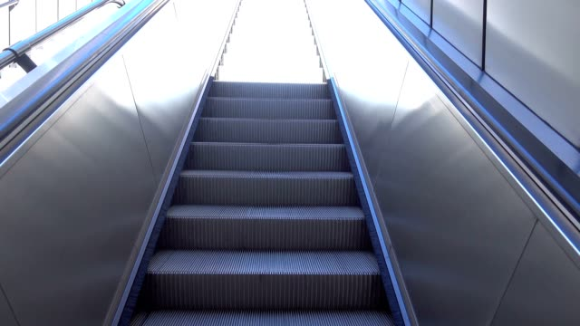 Electric escalators rising up to the white bright stairway to Heaven. video