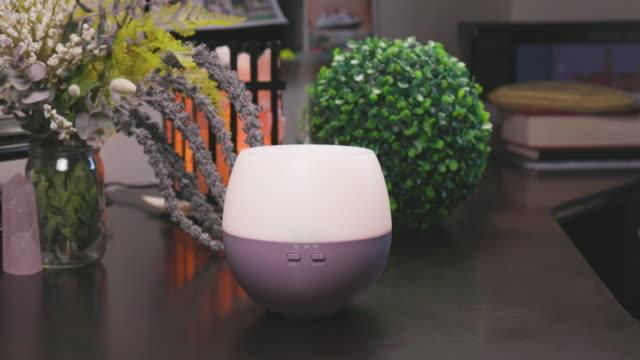 オイルバイアルと花に囲まれた電気エッセンシャルオイルアロマディフューザー - 加湿器点の映像素材/bロール