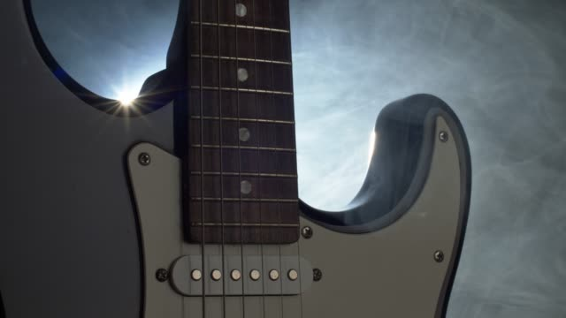 Electric guitar on the stage in soffits light and smoke before rock concert. Panning shot, 4K
