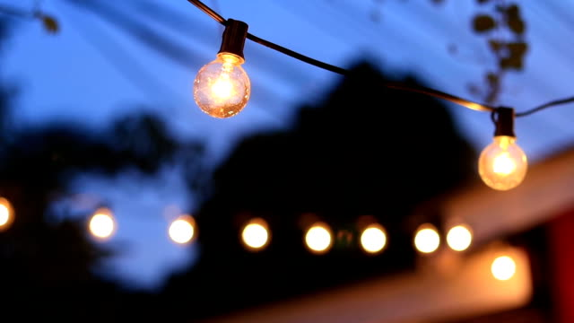 Electric lamps are hung on ceiling burns in darkness Electric lamps are hung on ceiling burns in darkness lamp shade stock videos & royalty-free footage