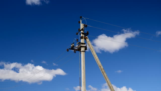 Electric line pylons against a blue sky.