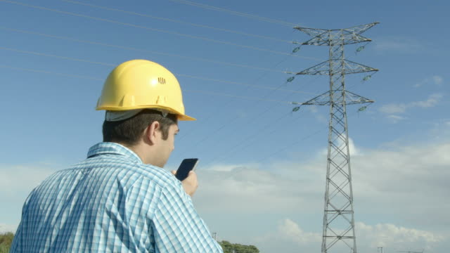 Electrical engineer in front of a power line. video