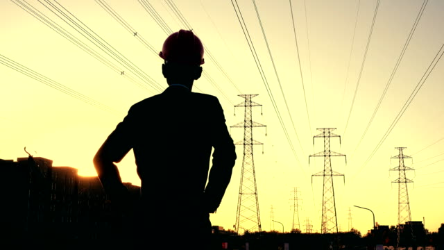 electrical engineer rear view at sunset - sottostazione elettrica video stock e b–roll