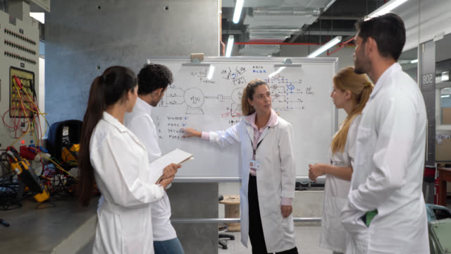 Electrical engineer teacher explaining something to students pointing at the white board and electrical board at the laboratory