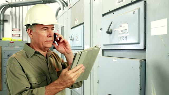 Ingeniero en electricidad con tablet pc y teléfono - vídeo