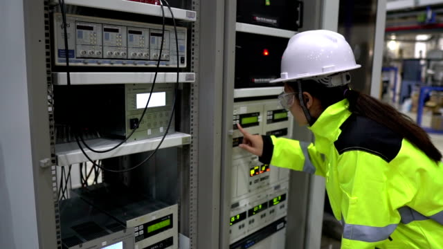 electrical engineer woman checking voltage - sottostazione elettrica video stock e b–roll