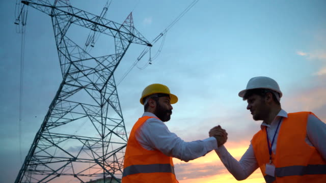 electrical engineers doing high five after successful work - centrale elettrica video stock e b–roll